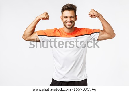 Strong happy, enthusiastic handsome bearded man in sports t-shirt, activewear, raise hands and brag  Stock photo © benzoix