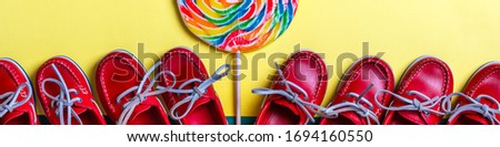 Small red boat shoes near big multi-colored lollipop and rope on colored background.  Top view. Clos Stock photo © Illia