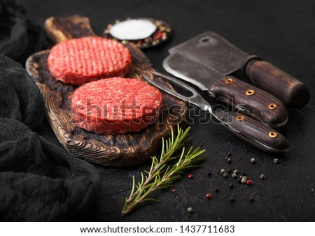 Fresh raw minced pepper beef burgers on vintage chopping board with spices and herbs and meat hatche Stock photo © DenisMArt