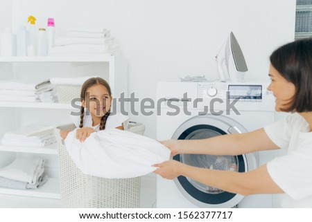 Happy girl with two pigtails poses in basket with dirty linen, has fun in laundry room with mother,  Stock photo © vkstudio