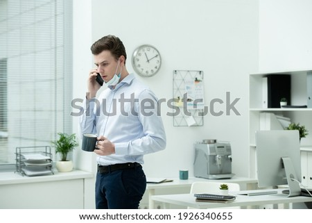 Young successful businessman with cup of tea consulting client by mobile phone Stock photo © pressmaster
