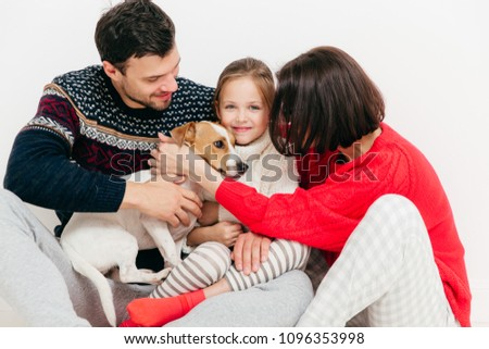 Three family members bought pedigree jack russell terrier dog, have happy expressions, isolated on w Stock photo © vkstudio