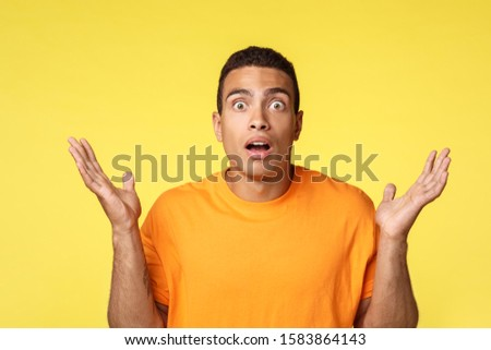 Impressed and frustrated young man lost bet in game, spread hands sideways dismay or indesicive gest Stock photo © benzoix