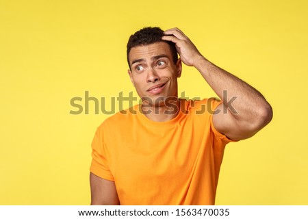 Unsure, clumsy young slightly dumb guy in casual t-shirt, scratching head clueless smirk and look aw Stock photo © benzoix