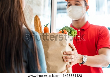 Courier, delivery man  delivers online purchases during the coronavirus epidemic. Stock photo © Illia