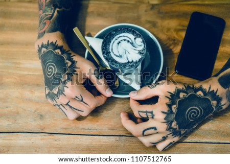 A male barista with a tattoo pours fresh milk into a glass with ice and coffee. Stock photo © artjazz