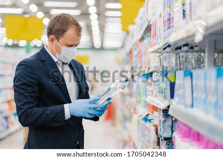 Photo of man dressed in formal suit, covers mouth with medical mask, wears rubber gloves to prevent  Stock photo © vkstudio