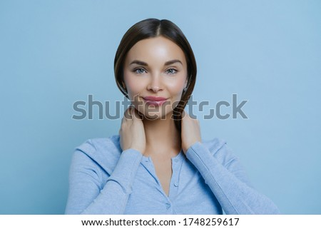 Headshot of young lovely woman keeps hands on neck, has European appearance, happy to hear pleasant  Stock photo © vkstudio