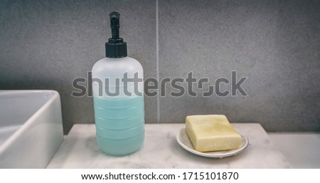 Soap bar versus liquid hand soap bottle comparison of hand washing products on home bathroom vanity  Stock photo © Maridav