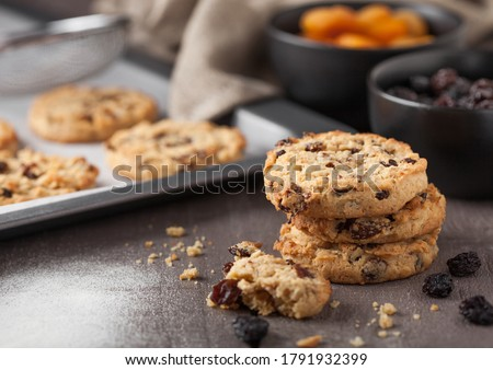 Homemade organic oatmeal cookies with raisins and apricots on wooden background. Black bowl of flour Stock photo © DenisMArt