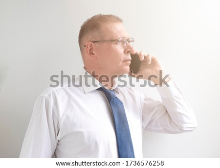 Businessman listening closely to caller against a white background Stock photo © wavebreak_media