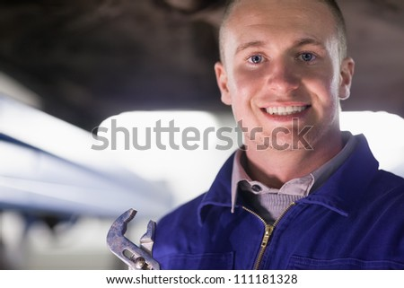 Mechanic holding an adjustable pliers while looking at camera in a garage Stock photo © wavebreak_media