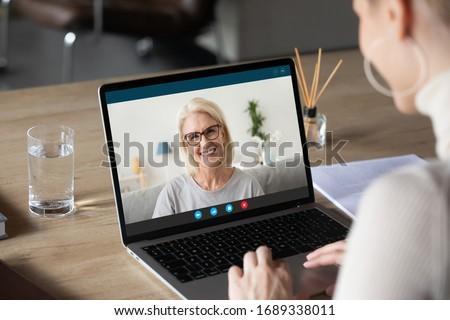 женщину используя ноутбук глядя камеры Сток-фото © deandrobot
