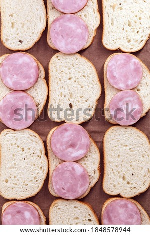 one slice of wheat bread and slices of sausage isolated on white stock photo © tetkoren