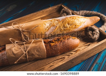two white baguette homemade bread on the table with rye spikelet and oats stock photo © mcherevan