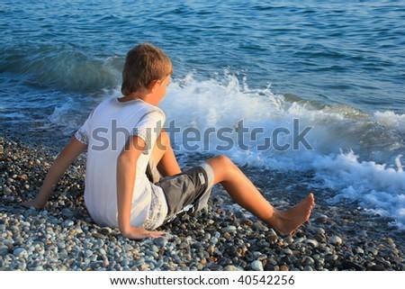 sitting teenager boy on stone seacoast, wets feet in water, sitt Stock photo © Paha_L