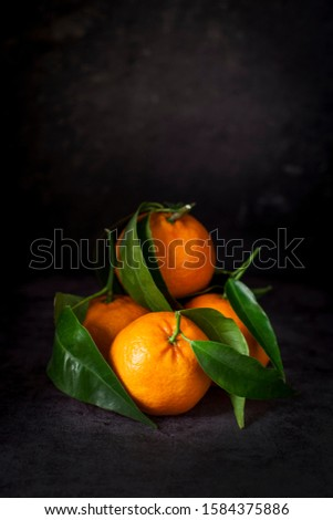 Fresh juicy tasty Sicilian tangerine with a foliage branch on a stone background. Stock photo © mcherevan