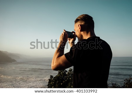 Man makes photos by a smartphone on the background of sea coast, Stock photo © vlad_star