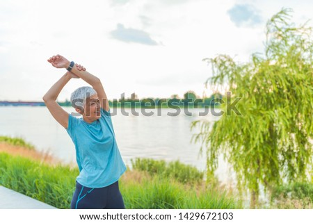 portrait of a smiling sports woman standing and stretching leg stock photo © deandrobot