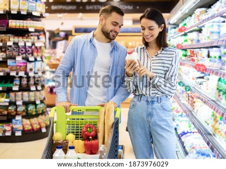 Happy woman doing shopping and buying yoghurt in grocery store Stock photo © deandrobot