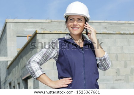worried female contractor wearing hard hat on site using cell ph stock photo © feverpitch