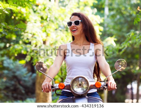 The happy young woman on the scooter in city park in the summer Stock photo © Yatsenko