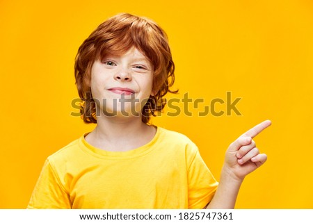 portrait of cute boy with orange shirt gesturing with his arms Stock photo © meinzahn