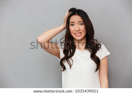 attractive young asian woman posing over white wall with plants stock photo © deandrobot