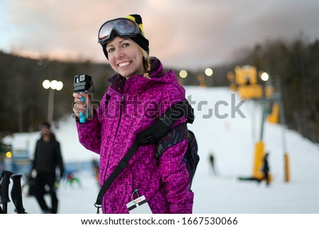 young beautiful woman in purple ski coat and goggles hold snowbo stock photo © traimak