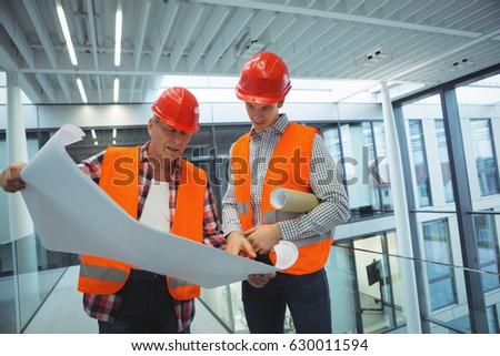 Architect in hard hat standing with blueprint in office corridor Stock photo © wavebreak_media