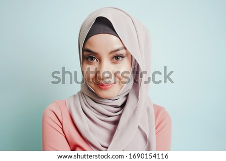 Portrait of beautiful serious young muslim woman wearing black hijab with closed eyes as praying con stock photo © Traimak