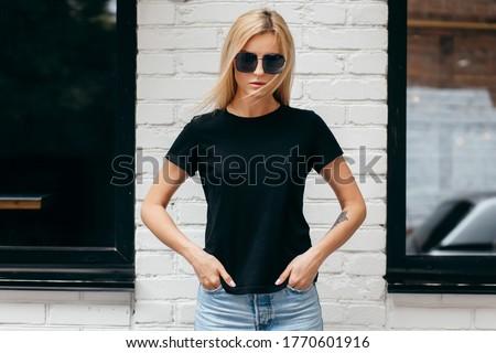 Portrait of a beautiful teenager wearing black glasses, a black waistcoat and light jeans. The teena Stock photo © Traimak