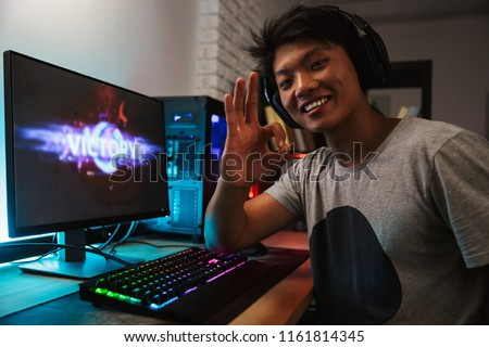 Excited smiling gamer boy rejoicing victory while playing video  Stock photo © deandrobot
