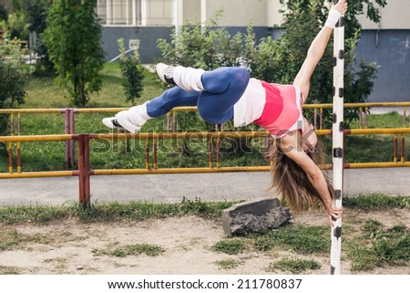 Young  brunette woman doing pull-up on a sports horizontal bar a Stock photo © boggy