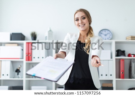 A young girl stands in the office next to the rack, holds documents and a pen in her hand and shows  Stock photo © Traimak