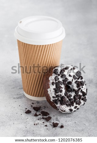 Cardboard coffee cup with black cookies doughnut on stone kitchen table background. Cafe drink and s stock photo © DenisMArt