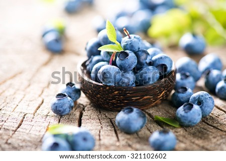Fresh raw organic blueberries with leaf in wooden bowl on white background. Macro Stock photo © DenisMArt