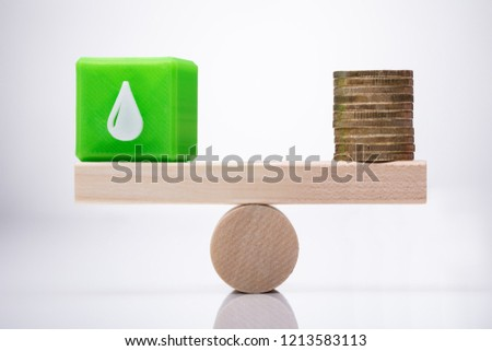 Cubic Block With Waterdrop Icon And Coins Balancing On Seesaw Stock photo © AndreyPopov
