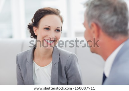 smiling businesswoman talking to her colleague in bright office stock photo © boggy