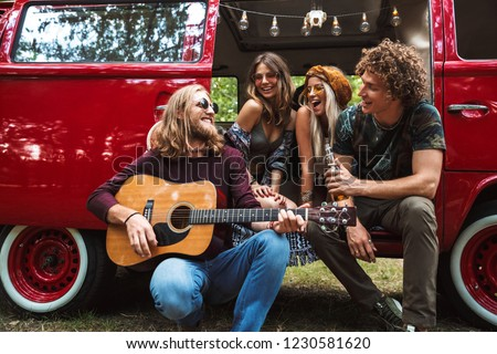 group of friends hippies men and women playing guitar and sitti stock photo © deandrobot