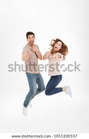 Full length photo of joyous couple man and woman jumping while p Stock photo © deandrobot