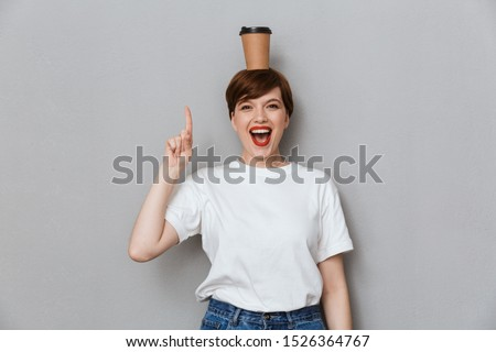 woman posing isolated over grey wall background drinking coffee talking by mobile phone stock photo © deandrobot