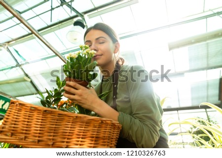 image of young florist woman 20s wearing apron smelling plant fr stock photo © deandrobot