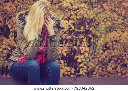 A Sad woman in park during autumn weather hiding face in hand, feeling terrible depressed. Stock photo © Lopolo