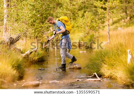 young man crosses a mountain stream during a hiking on a sunny d stock photo © boggy