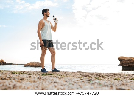 Stock photo: Handsome young sports man standing on the beach drinking water.