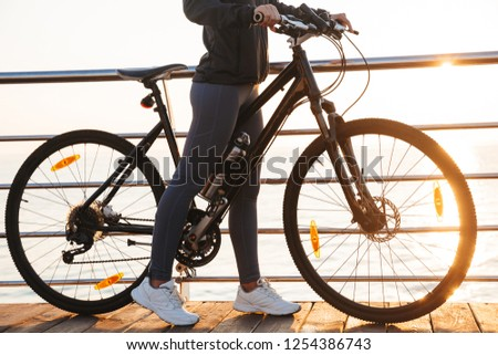 Photo of sportive woman standing with bicycle on boardwalk, duri Stock photo © deandrobot