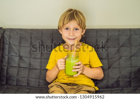 The boy is drinking Green tea latte with ice in mason jar. Homem Foto stock © galitskaya