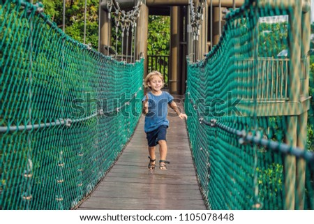 The boy is running on a suspension bridge in Kuala Lumpur, Malaysia Stock fotó © galitskaya