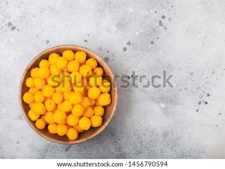 Puffed golden cheese balls as classic kids snack on light background. Stock photo © DenisMArt
